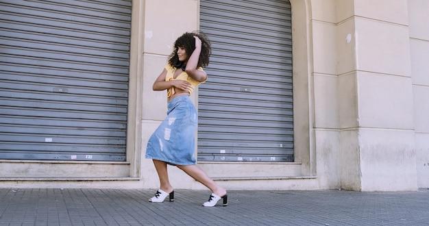通りで踊る彼女の頭の上にアフロを持つモダンなスタイルのダンサー