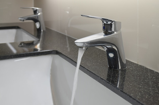 Modern style faucet with under counter wash basin in restroom