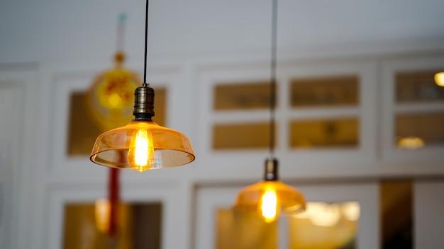 モダンなスタイルのランプが天井または天井ランプからぶら下がっていて、金色に照らされています。ホームインテリアのアイデア。