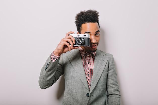 Ragazzo moderno ed elegante americano-africano in posa sul muro bianco con una fotocamera retrò e prende le riprese su grigio