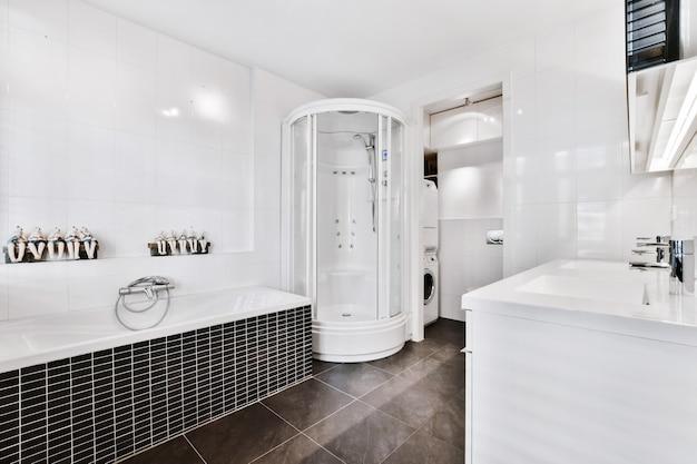 Современный стильный дизайн интерьера ванной комнаты с мраморным полом и белой мебелью с угловой ванной и душевой кабиной.