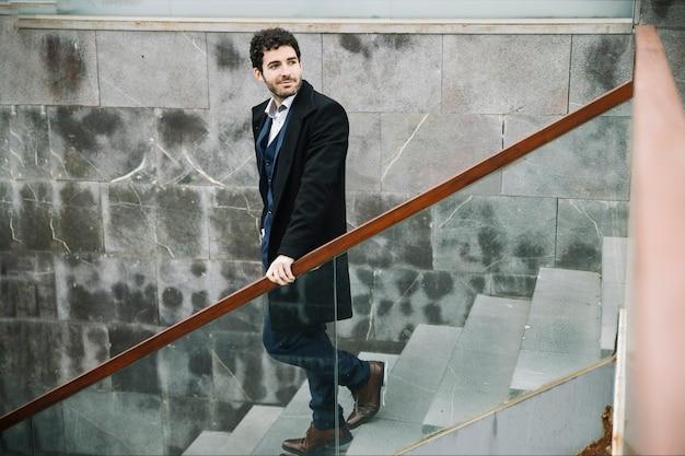 Modern and stylish businessman walking upstairs