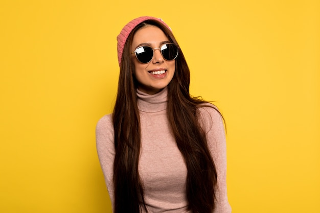 Modern stylish hipster female with long dark hair wearing pink cap and round sunglasses posing with happy smile