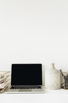 空白のモックアップ画面のラップトップ、白の文房具とモダンでスタイリッシュなホームオフィスデスクワークスペース