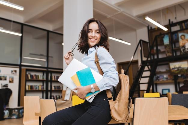 Immagine moderna ed elegante della giovane donna castana intelligente con il computer portatile sul tavolo in libreria. sorridente, gioco con occhiali neri, grande successo, studente laborioso.