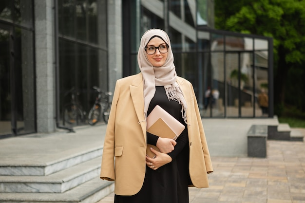 Modern stylish muslim woman in hijab, business style jacket and black abaya walking in city street with laptop