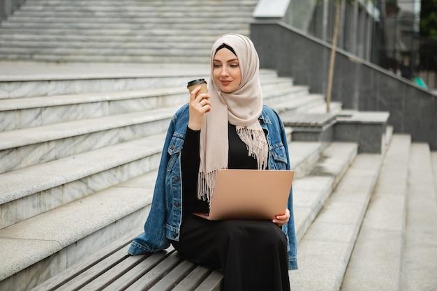 Modern stylish muslim woman in hijab, denim jacket and black abaya sitting in city street working on laptop