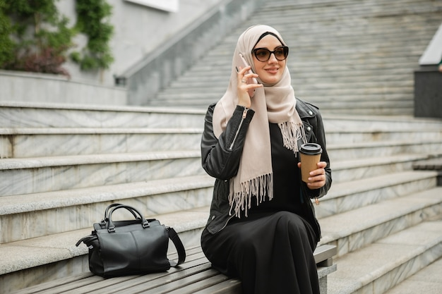 Modern stylish muslim woman in hijab, leather jacket and black abaya sitting in city street talking on mobile phone in sunglasses