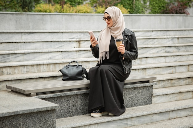 Modern stylish muslim woman in hijab, leather jacket and black abaya sitting in city street with mobile phone in sunglasses