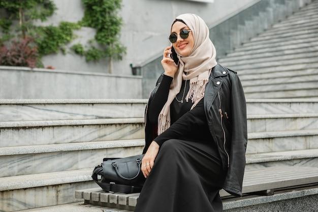 Modern stylish muslim woman in hijab, leather jacket and black abaya walking in city street talking on smartphone