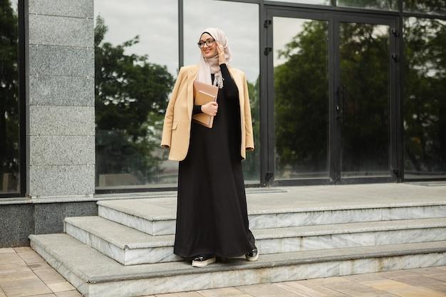 Hijab, 비즈니스 스타일 재킷 및 노트북과 도시 거리에서 산책하는 검은 아바야에 현대적인 세련 된 이슬람 여성