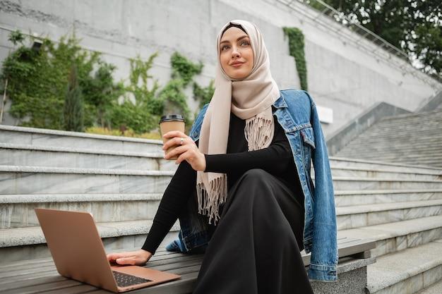 ヒジャーブ、デニム ジャケット、ノート パソコンに取り組んでいる街の通りに座っている黒いアバヤでモダンなスタイリッシュなイスラム教徒の女性