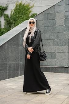 Hijab, 가죽 자켓 및 도시 거리에서 걷고있는 검은 색 아바야의 현대적인 세련된 이슬람 여성