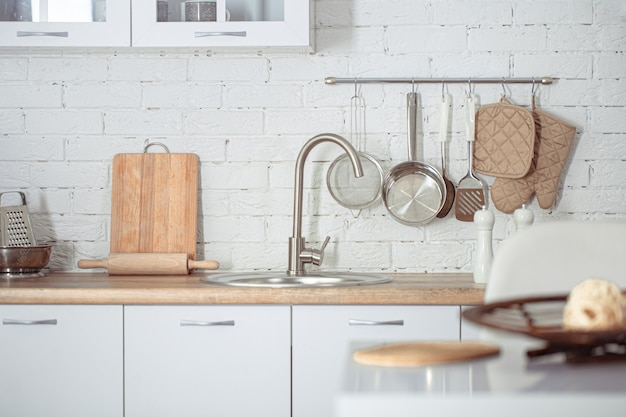 キッチンアクセサリーとモダンなスタイリッシュなスカンジナビアキッチンインテリア。家庭用品を備えた明るい白いキッチン。