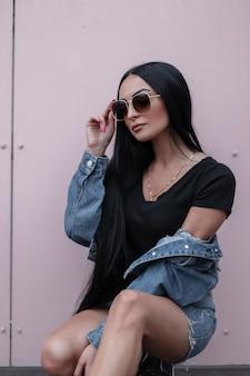 선글라스 v 유행 데님 옷에 현대적인 세련 된 젊은 갈색 머리 여자는 여름 날에 거리에서 금속 빈티지 벽 근처에 앉아있다. 꽤 도시의 힙 스터 소녀. 트렌디 한 제철 여성복