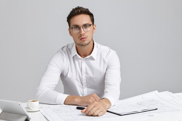 Giovane architetto capo di successo moderno di grande società di costruzioni che indossa camicia formale e occhiali rotondi