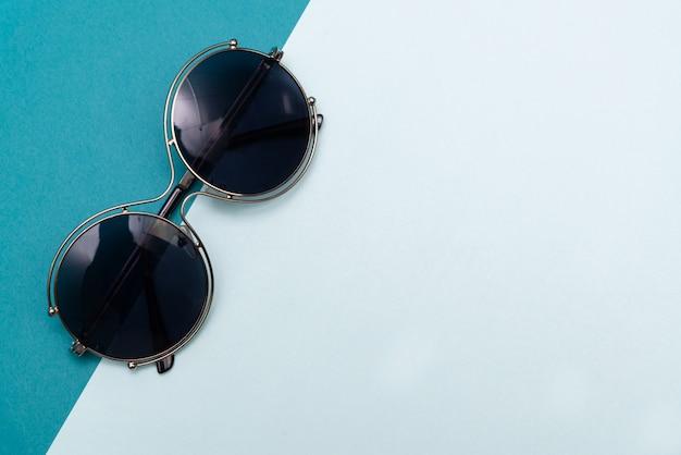 Modern sunglasses on pastel paper background