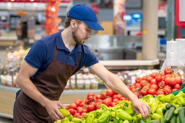 新鮮な野菜、水平ミディアムショットを設定する制服を着ている現代のスーパーマーケットの労働者
