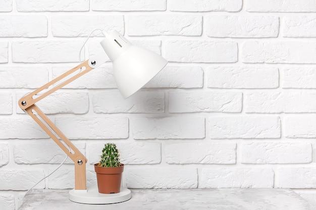 흰색 벽돌 벽의 배경에 대해 테이블에 현대적인 테이블 램프와 선인장. 직장, 전면 보기, 복사 공간.