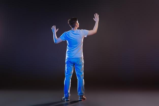現代の技術。透明な画面の近くに立っている間彼の前を見て喜んでいる素敵な男