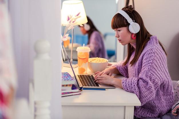 Современные технологии. сознательный подросток делает домашнее задание, сидя в полу-положении в своей комнате