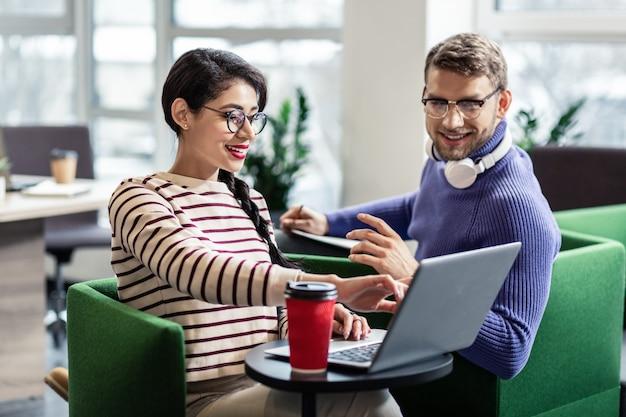 Современные технологии. довольный бородатый мужчина держит улыбку на лице, глядя на компьютер