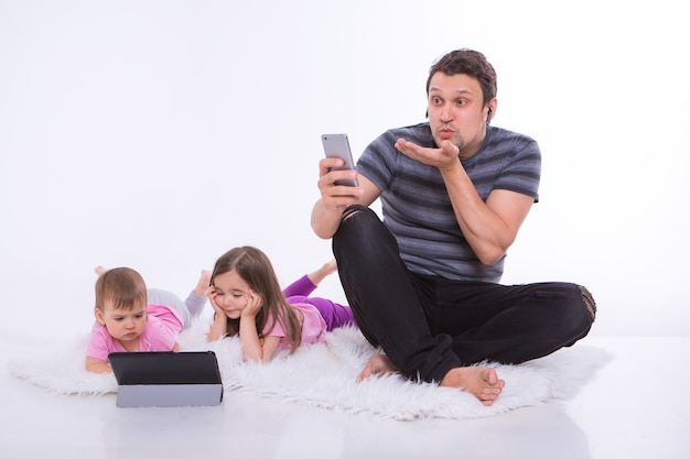 Modern technologies in everyday life: a man talks on the phone through a headset, children watch a cartoon on a tablet. hobbies and recreation with gadgets. parent with girls on the floor
