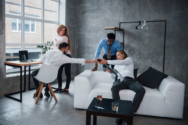 Modern technologies have become an integral part of the work. group of multiracial office workers in formal clothes talking about tasks and plans