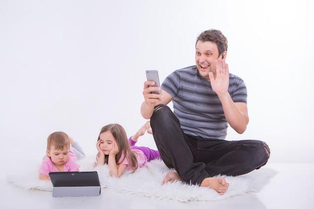 日常生活の現代技術:ヘッドセットを介して電話で話している男性、タブレットで漫画を見る子供たち。趣味とガジェットでのレクリエーション。床に女の子と親
