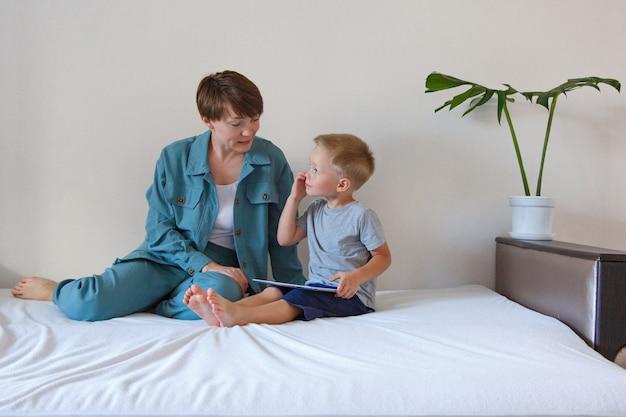 日常生活における現代のテクノロジー:女性と子供がベッドの上のタブレットを見る