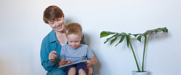 女性と子供が床に置いたタブレットを見る日常生活の現代技術。