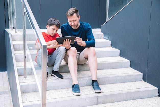 Современные технологии в жизни молодой семьи. отец и сын играют на планшете. стиль жизни.