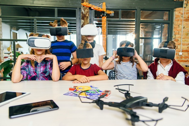 Modern technologies in a smart school. clever caucasian pupils use virtual reality glasses for education.