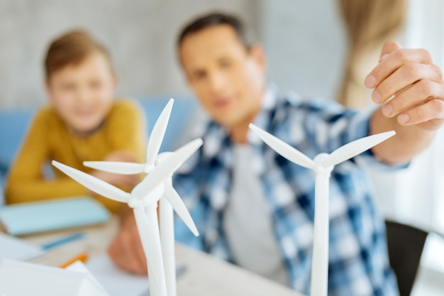 Современные технологии. в центре внимания находятся три ветряные турбины, стоящие на планшете и на которые указывает молодой отец, рассказывающий о них своим сыновьям.