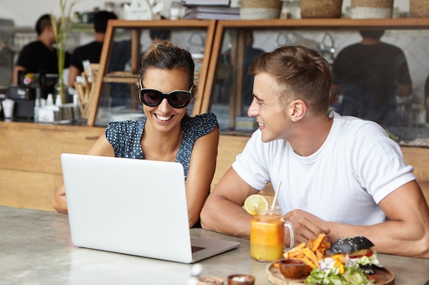 現代の技術とコミュニケーションの概念。幸せなカップルがカフェで昼食をとりながら一緒に一般的なラップトップで無料のwi-fiを使用してインターネットでビデオを見たり写真を閲覧したりします。セレクティブフォーカス