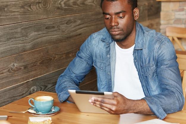 現代の技術とコミュニケーション。スタイリッシュなアフリカの学生がデジタルタブレットでインターネットをサーフィンし、コーヒーブレーク中にカフェで無料のワイヤレス接続を楽しんでいます。浅黒い肌の男性メッセージングオンライン