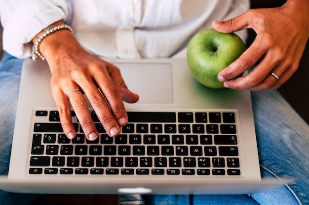 현대 기술 비즈니스 활동 개념과 사람들을위한 건강한 라이프 스타일-키보드 노트북 컴퓨터와 여성의 손 입력 위의보기-녹색 사과-캐주얼 의류-프리랜서 생활