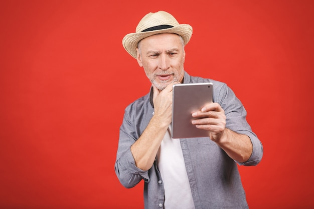 Modern technology concept. portrait of aged man trying to use digital tablet or e-book