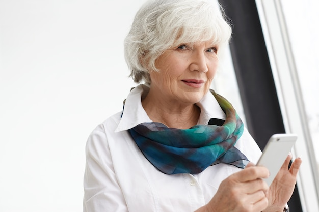 現代のテクノロジー、電子機器、年齢と退職の概念。スマートフォンを介してオンライン通信を楽しんで、smsを入力して白髪の魅力的なきちんとした白人女性年金受給者の写真