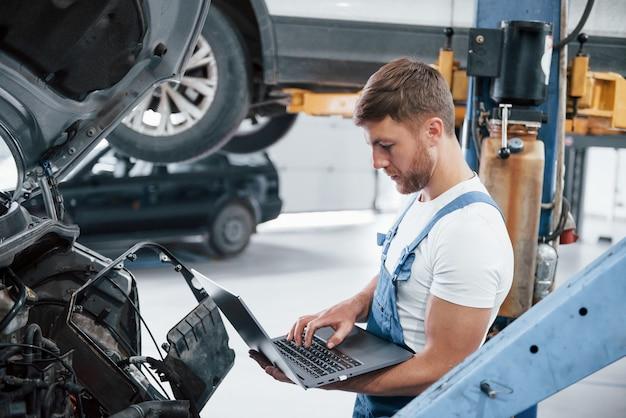 현대 기술. 파란색 유니폼을 입은 직원이 자동차 살롱에서 일합니다.