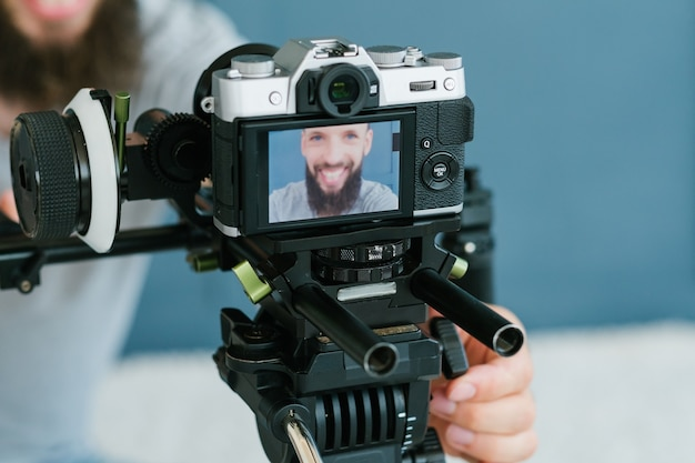 写真とビデオの撮影のための最新技術。三脚のカメラ。ブロガーの機器とツール。画面上の男の画像。