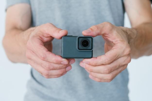 ビデオコンテンツ作成のための最新技術。手にアクションカメラを持っている認識できない男。ブロガー機器とツールのコンセプト。
