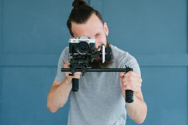 ビデオ撮影のための最新技術。カメラを持っている男。ブログや映像コンテンツを作成するための機器とツール。