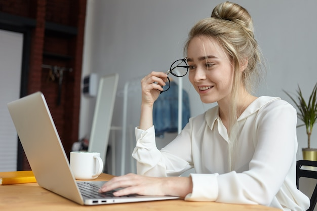 Modern technology, gadgets, job and communication concept. happy charming young woman with hair bun holding round eyeglasses and keyboarding on laptop pc, browsing internet, chatting online