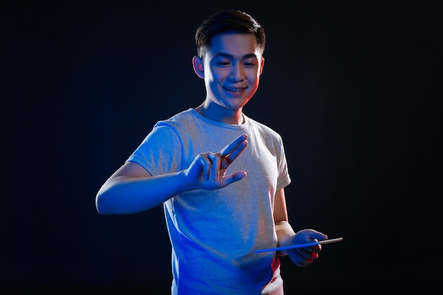 現代のテクノロジー。タブレットを持っている間彼の指を見てうれしそうな喜びの男
