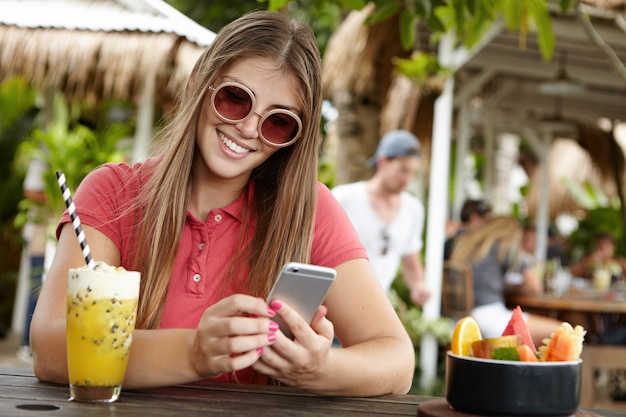 Modern technology, leisure and people concept. cute woman in shades texting messages to her friend using generic smart phone