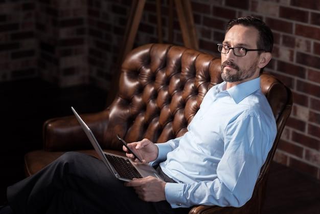 現代のテクノロジー。ソファに座って、膝の上にラップトップを持っている間彼の携帯電話を見ている素敵なハンサムなひげを生やした男
