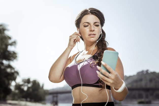 現代のテクノロジー。曲を選択しながらスマートフォンの画面を見ている素敵な真面目な女性