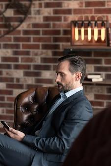 Современные технологии. симпатичный успешный привлекательный мужчина сидит в кресле и держит мобильный телефон, находясь в своем офисе