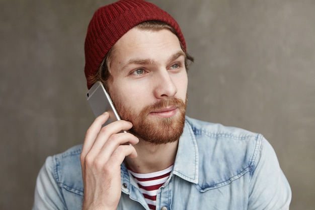 Modern technology, people and communication concept. headshot of fashionable bearded student in hat and denim shirt having nice conversation on smartphone, smiling while receiving positive news
